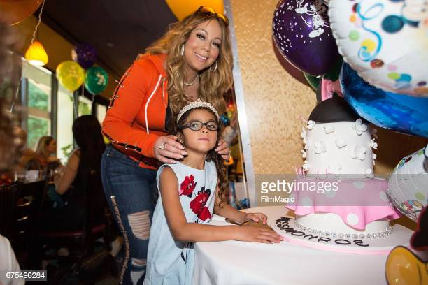 Monroe Cannon poses next to her birthday cake as mom Mariah Carey looks on at Disneyland on April 30 2017 in Anaheim California