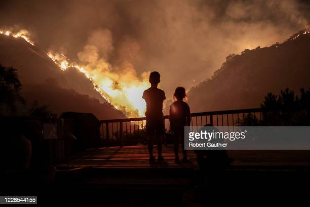 Monrovia, CA, September 15, 2020 - Iris and Castle Snider look on as flames engulf the hillsides behind their backyard as the Bobcat Fire burns near...