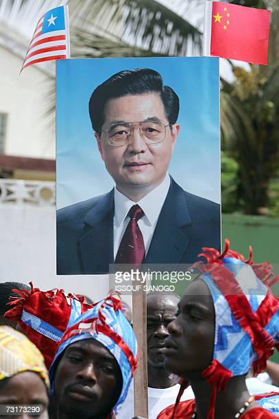 Liberians hold a poster of Chinese President Hu Jintao as the Head of State arrived in Monrovia for a one-day visit to Liberia, 01 February 2007, on...