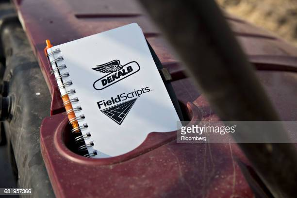 A Monsanto Co Dekalb logo is displayed on a notebook near a corn field in Princeton Illinois US on Tuesday May 2 2017 US inventory of corn and wheat...