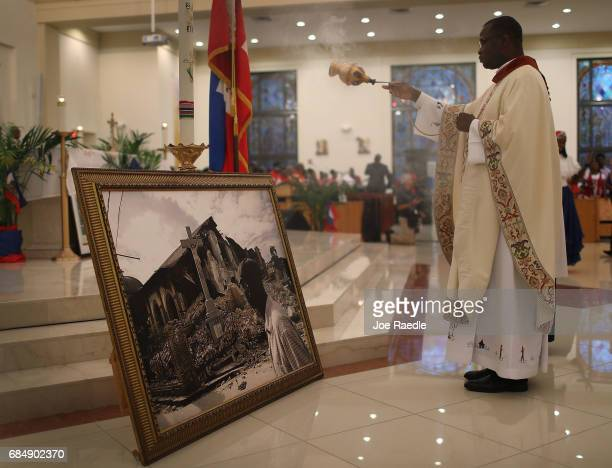 Monsignor Chanel Jeanty uses a censer near a framed picture of a church that was destroyed by the massive 2010 Earthquake in Haiti during a service...
