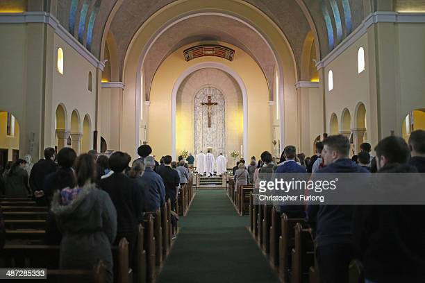 Monsignor Paul Fisher conducts mass for members of the local community attending Corpus Christ Catholic Church to pray and pay their respects to...