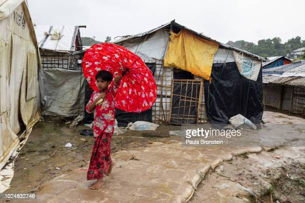Monsoon rains hit the refugee camps as a girl carries her umbrella August 28 2018 in Unchiprang refugee camp Cox's Bazar Bangladesh UN investigators...