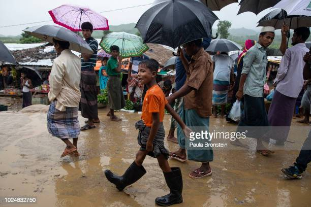 Monsoon rains hit the refugee camps as Rohingya walk through a local market August 28 2018 in Unchiprang refugee camp Cox's Bazar Bangladesh UN...