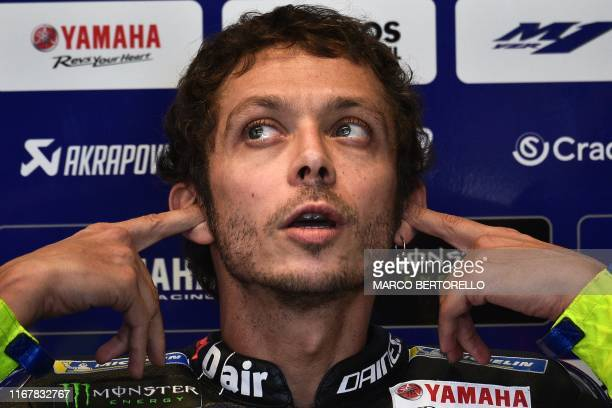 Monster Energy Yamaha Italian rider Valentino Rossi covers his ears as he sits in the stands during a free practice session ahead of the San Marino...