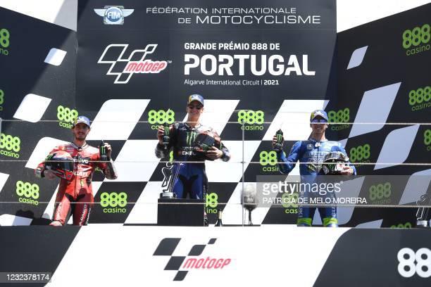 Monster Energy Yamaha MotoGP's French rider and winner Fabio Quartararo poses on the podium with Ducati Lenovo Team's second-placed Italian rider...