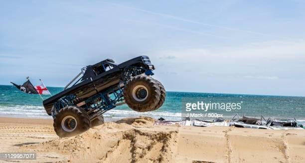 monster truck driving over car wrecks on sandy coastal beach - monster truck stock pictures, royalty-free photos & images