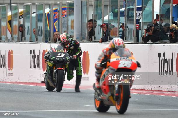 Monster Yamaha Team's French rider Johann Zarco pushes his bike across the finish line during the San Marino Moto GP Grand Prix at the Marco...