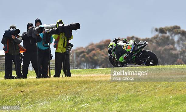 Monster Yamaha Tech 3 Spanish rider Pol Espargaro powers past photographers during the qualifying session of the MotoGP class at the Australian Grand...