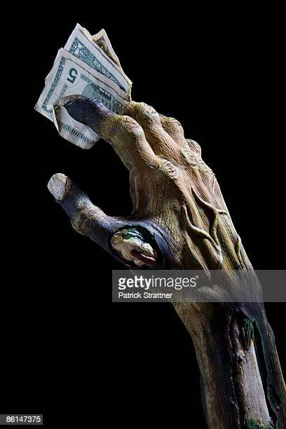 Monster's hand holding money