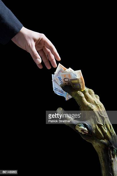 Monster's hand passing money to a businessman