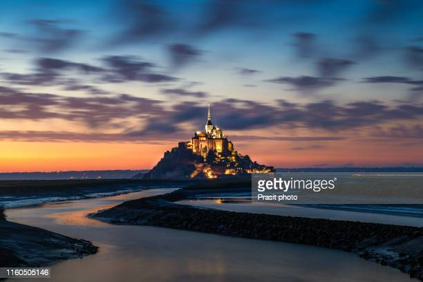 mont saint michel illuminated architecture panoramic beautiful postcard view at dusk in summer low tide from the bridge with reflection, normandy, france - cotentin photos et images de collection
