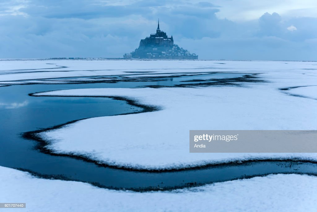 Mont Saint-Michel (Saint Michael's Mount), Normandy, north-western France: Le Mont Saint-Michel and its abbey in the morning mist and snow. Drawing depicting the channels and the salt marshes in the bay.