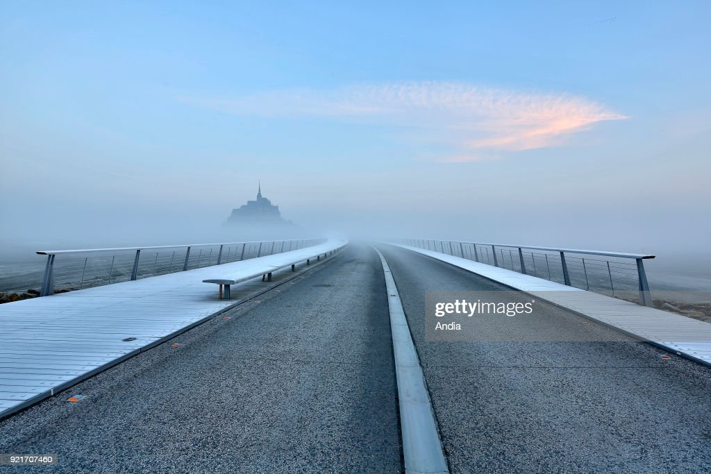 Mont Saint-Michel (Saint Michael's Mount), Normandy, north-western France: Le Mont Saint-Michel in the morning mist, viewed from the footbridge in winter.