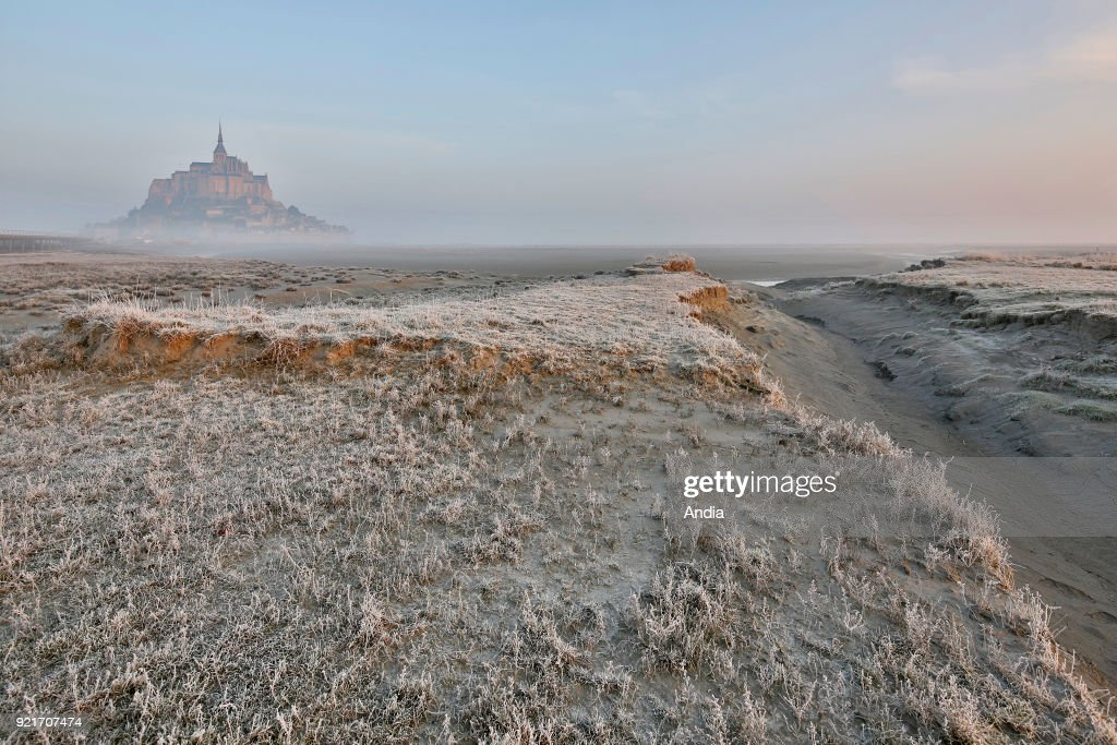 Mont Saint-Michel (Saint Michael's Mount), Normandy, north-western France: Le Mont Saint-Michel in the morning mist, viewed from the footbridge in winter. The bay at low tide.