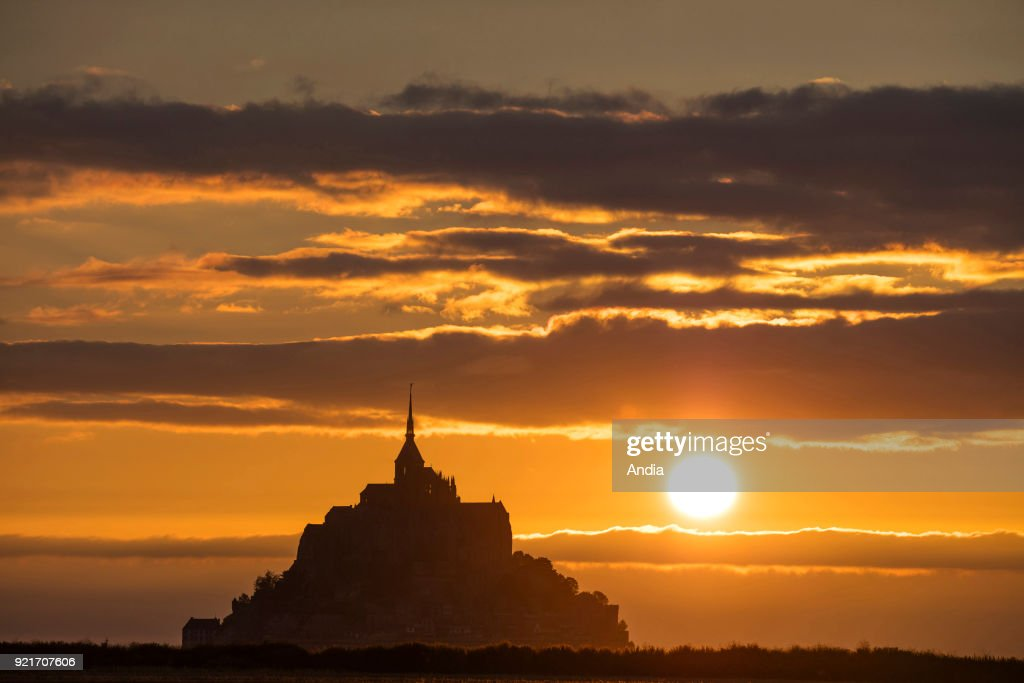 Mont Saint-Michel (Saint Michael's Mount), Normandy, north-western France: silhouette of the mount and the abbey and sunset over the bay.