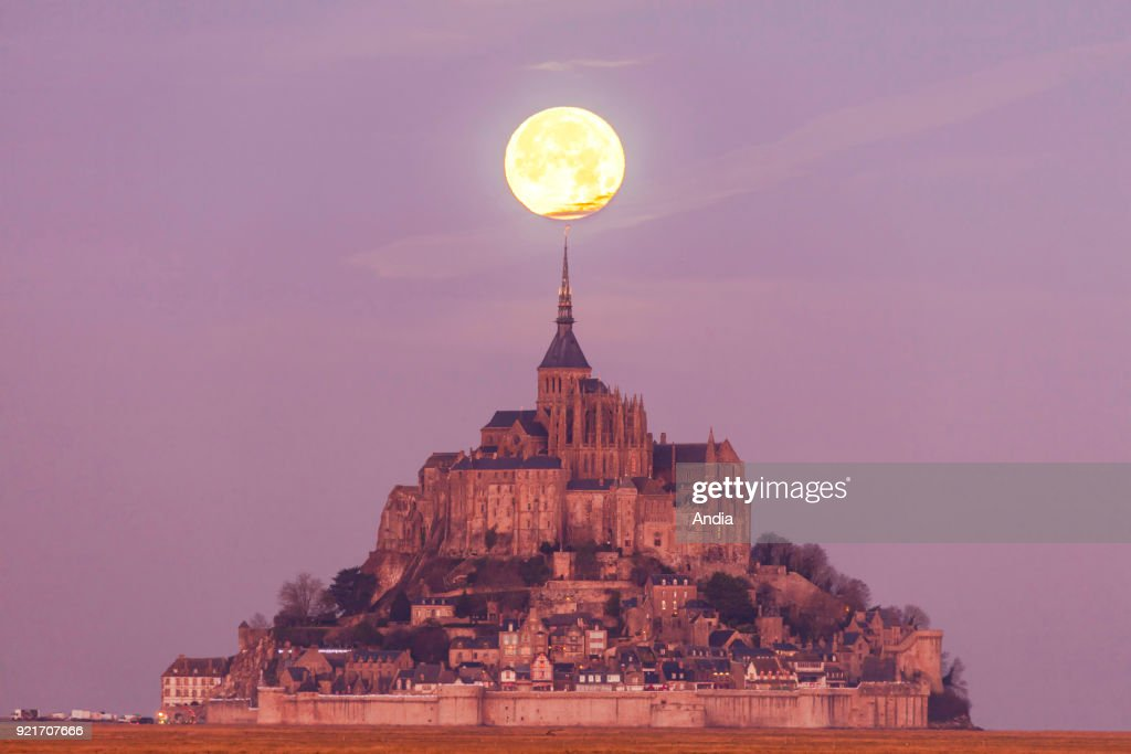 Mont Saint-Michel (Saint Michael's Mount), Normandy, north-western France: the moon over the mount at sunrise.