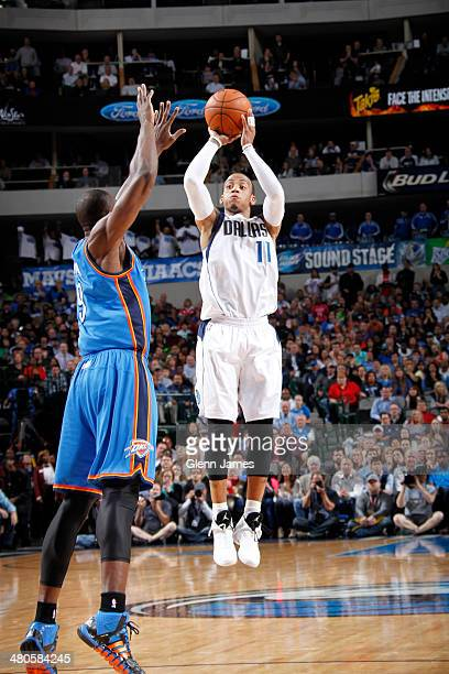 Monta Ellis of the Dallas Mavericks shoots against Serge Ibaka of the Oklahoma City Thunder on March 25 2014 at the American Airlines Center in...