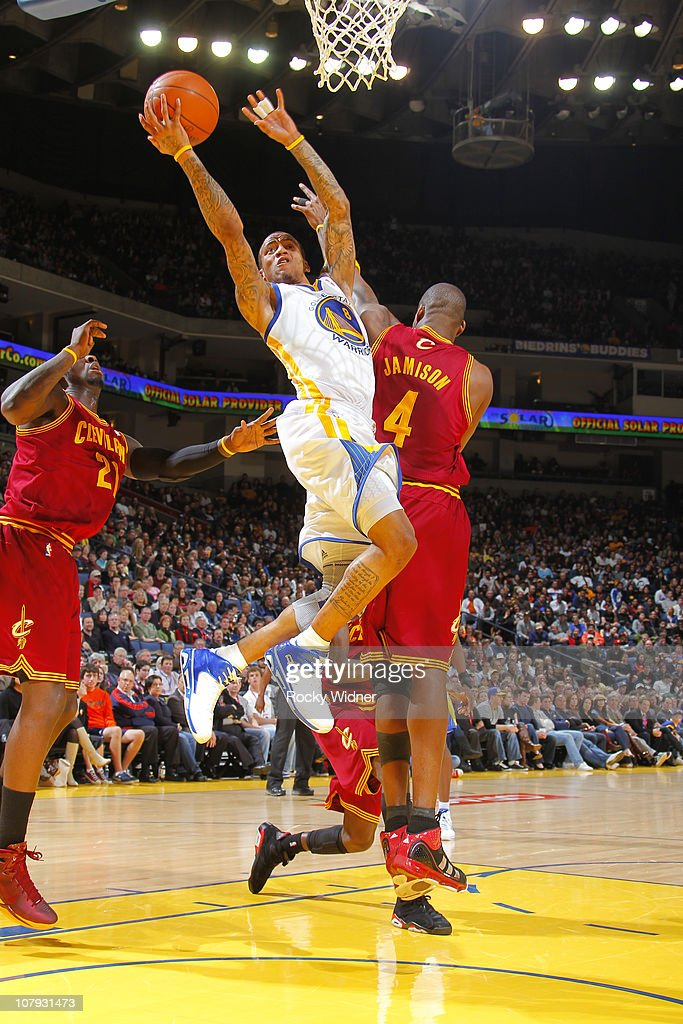 Monta Ellis #8 of the Golden State Warriors attempts a layup over Antawn  Jamison #