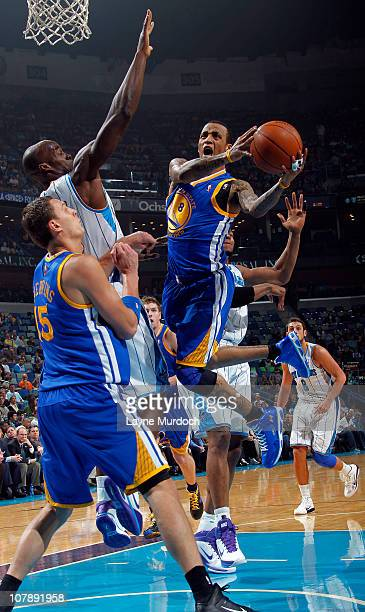 Monta Ellis of the Golden State Warriors attempts a layup while being guarded by Emeka Okafor of the New Orleans Hornets on January 5 2011 at the New...