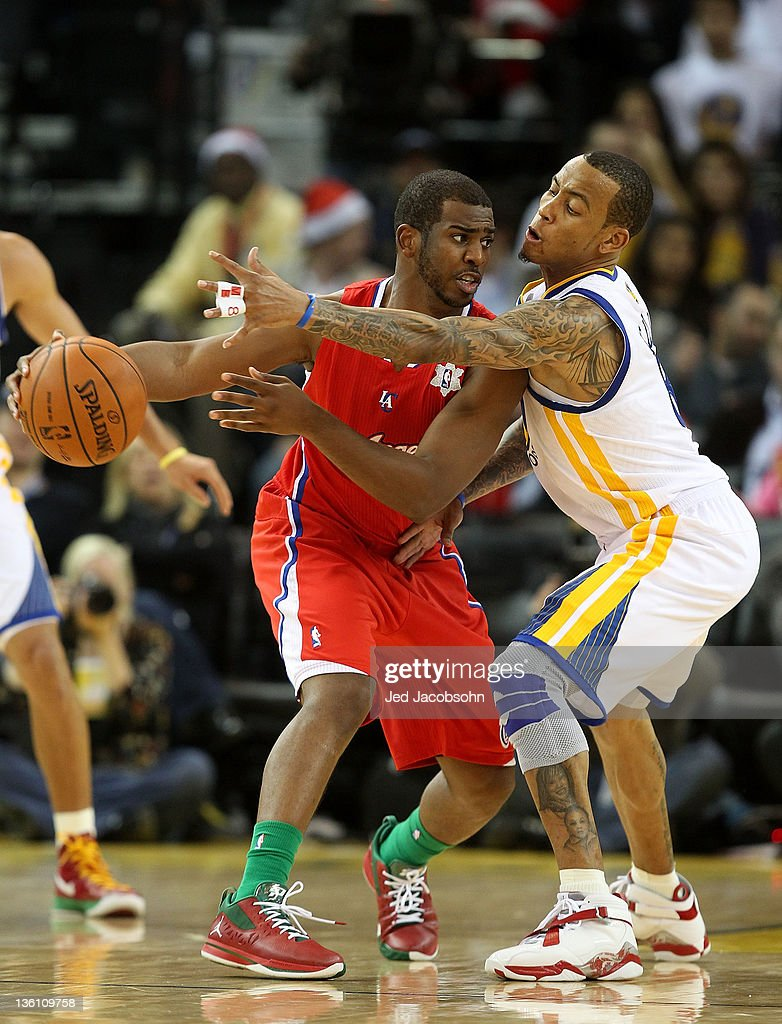 Monta Ellis #8 of the Golden State Warriors defends Chris Paul #3 of the Los Angeles Clippers during the season opener at Oracle Arena on December 25, 2011 in Oakland, California.