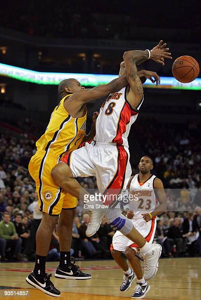 Monta Ellis of the Golden State Warriors is fouled by Earl Watson of the Indiana Pacers at Oracle Arena on November 30 2009 in Oakland California...