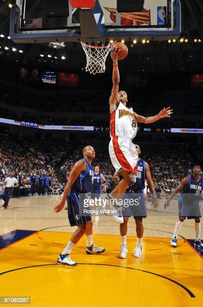Monta Ellis of the Golden State Warrriors shoots a layup past Devean George and Malik Allen of the Dallas Mavericks during the game at Oracle Arena...