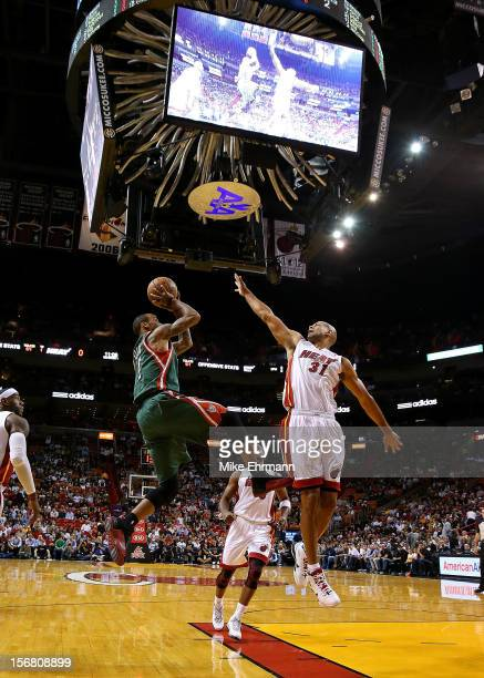 Monta Ellis of the Milwaukee Bucks shoots over Shane Battier of the Miami Heat during a game at AmericanAirlines Arena on November 21 2012 in Miami...