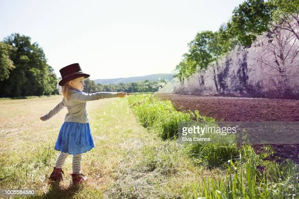 montage of child dressed as magician changing a summer field into a frozen winter scene - zaubertrick stock-fotos und bilder