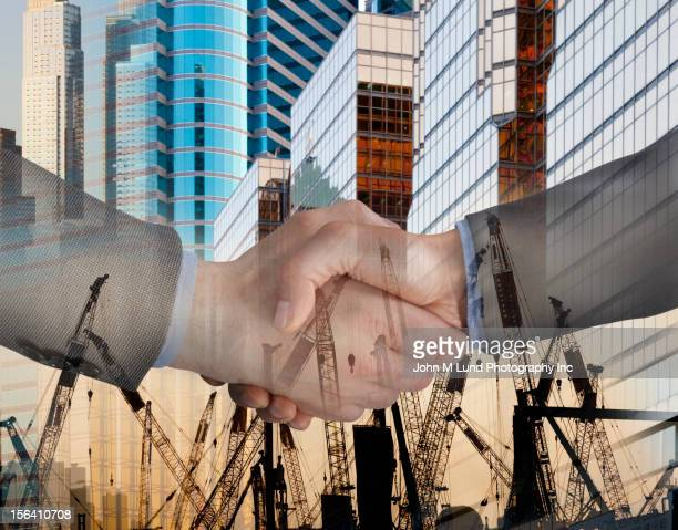 Montage of highrise buildings, cranes and businessmen shaking hands