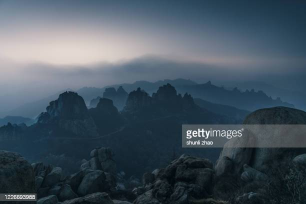 montains winded by fog at night - moody sky stock pictures, royalty-free photos & images