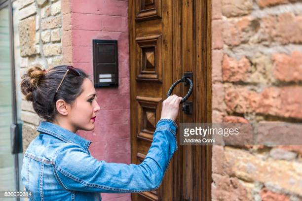 montalcino, siena, tuscany. a girl knocking at a door - knocking on door stock photos and pictures