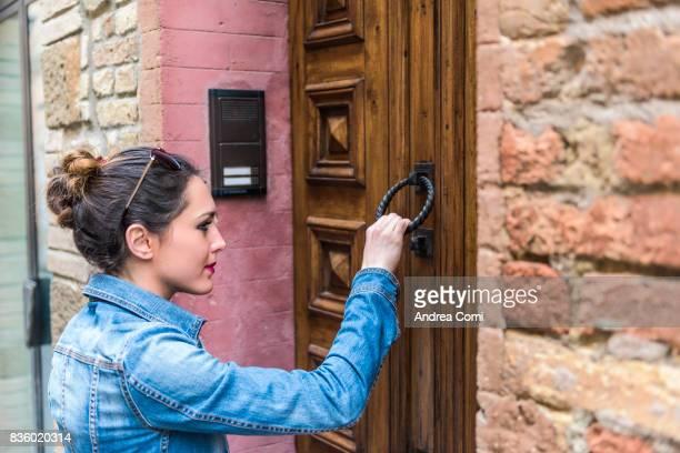 Montalcino, Siena, Tuscany. A girl knocking at a door