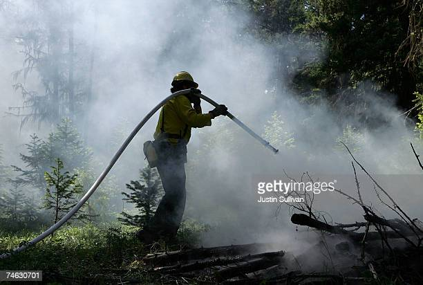 Montana Department of Natural Resources and Conservation firefighter Will Wood uses a hose to put out a fire during a live fire training at the...
