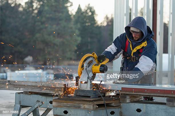 USA, Montana, Kalispell, Man cutting steel bar