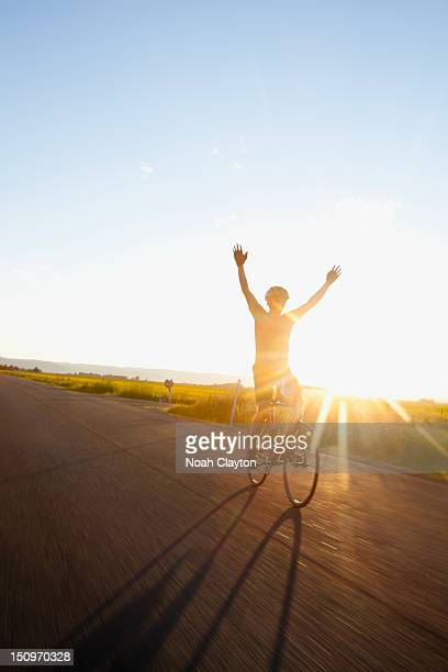 usa, montana, kalispell, silhouette of cyclist holding arms up - hands free cycling stock pictures, royalty-free photos & images