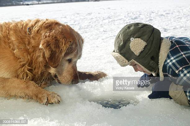 USA, Montana, Kila, boy (6-8) and dog ice fishing, side view