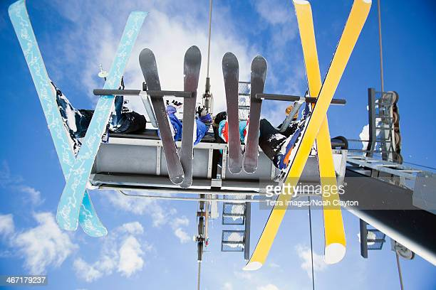 usa, montana, whitefish, family of skiers on ski lift seen from below - ski lift stock pictures, royalty-free photos & images