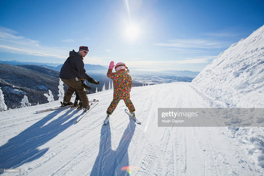 USA, Montana, Whitefish, Father skiing with children (6-7, 8-9) : Stock Photo