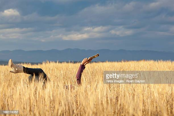 USA, Montana, Whitefish, Woman lying in field holding digital tablet