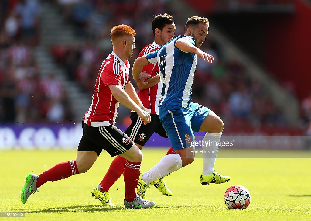 Montanes of Sevilla holds off pressure form Harrison Reed (L) and Juanmi (C) of Southampton during the pre season friendly match between Southampton and Espanyol at St Mary's Stadium on August 2, 2015 in Southampton, England.