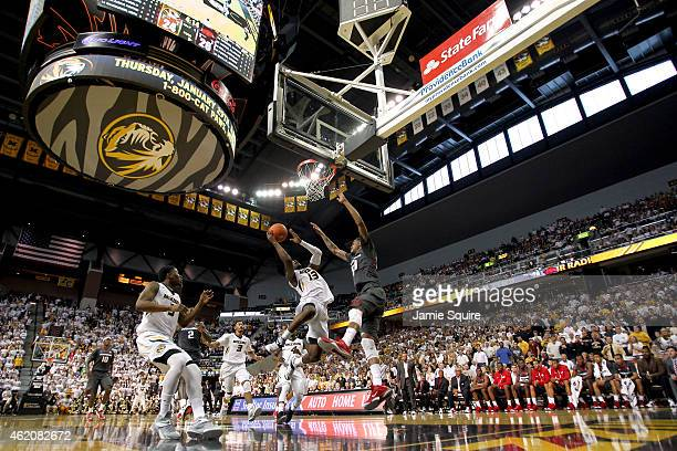 Montaque Gill-Caesar of the Missouri Tigers shoots while Rashad Madden and Alandise Harris of the Arkansas Razorbacks defend during the game at...