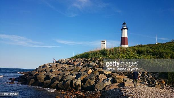 montauk point light on shore against sky - long island stock pictures, royalty-free photos & images