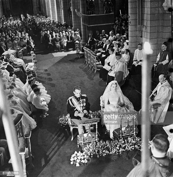 Monte Carlo, Monaco: Flower girls, page boys, and bridesmaids sit in the background and Prince Rainier and Grace Kelly sit before the altar during...
