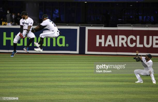 Monte Harrison and Lewis Brinson leap in the air as Starling Marte of the Miami Marlins takes a mock photo after winning against the Philadelphia...