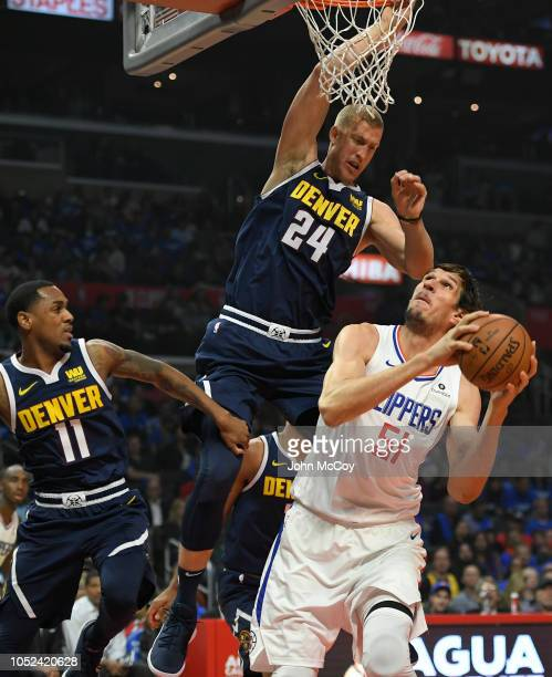 Monte Morris and Mason Plumlee of the Denver Nuggets guard Boban Marjanovic of the LA Clippers in the first half during the season opening game at...