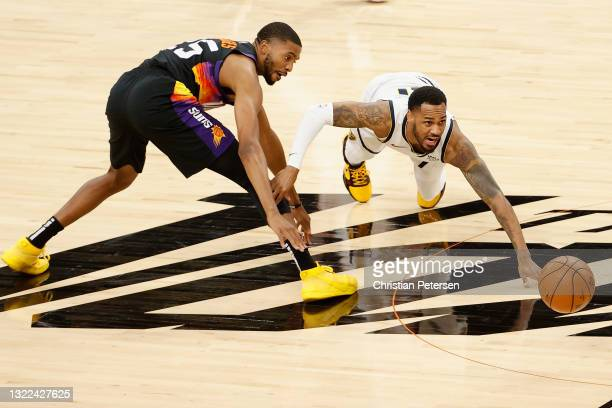 Monte Morris of the Denver Nuggets and Mikal Bridges of the Phoenix Suns battle for a loose ball during the first half in Game One of the Western...