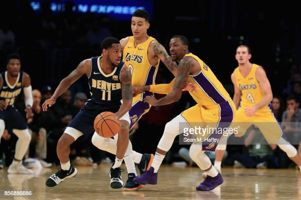 Monte Morris of the Denver Nuggets dribbles away from Kyle Kuzma and Kentavious CaldwellPope of the Los Angeles Lakers during the second half of a...