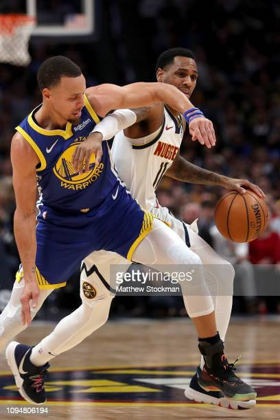 Monte Morris of the Denver Nuggets is guarded by Stephen Curry of the Golden State Warriors at the Pepsi Center on January 15 2019 in Denver Colorado...