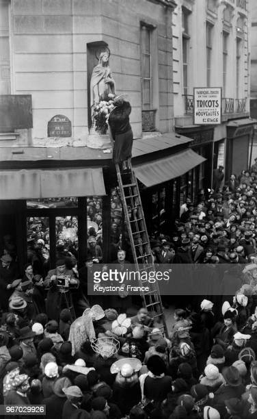 Montée sur une échelle une catherinette fleurit la statue de la SainteCatherine à Paris France le 25 novembre 1933